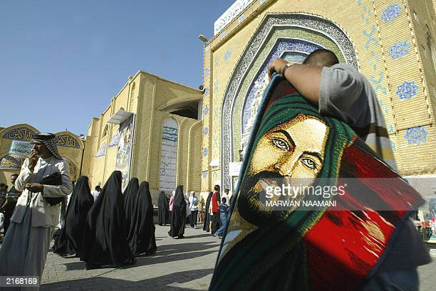 A man sells carpets with the Image of Imam Ali the soninlaw of Islam's prophet Mohammed ouside the alKazemiyah mosque in north Baghdad 11 July 2003...
