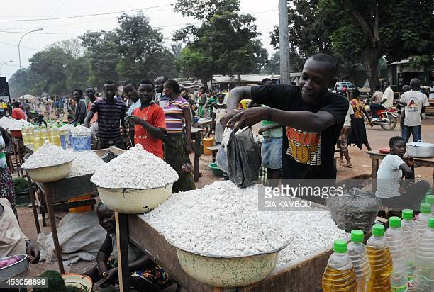 A man sells cassava root flour at his stall in a market in Bangui on December 2 2013 More than 200 French troops begin today the hard task of...