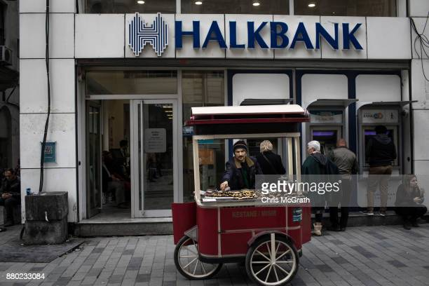 A man sells chestnuts in front of a branch of the Turkish Halk Bank on November 27 2017 in Istanbul Turkey The trial of Mr Reza Zarrab an IranianTurk...