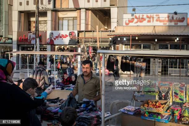 A man sells clothing at a market stall in East Mosul on November 5 2017 in Mosul Iraq Five months after Mosul Iraq's secondlargest city was liberated...