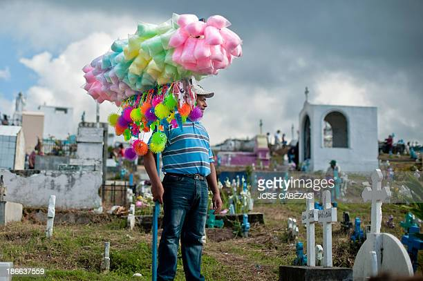 A man sells cotton candy at a cemetery in Panchimalco 18 kms south of San Salvador on November 2 2013 during the commemoration of the day of the dead...