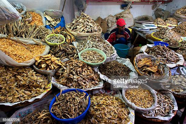 A man sells dried fish at Iewduh Bazar in Shillong Meghalaya Lewduh also known as Bara Bazar is a bustling marketplace in Shillong that earns immense...