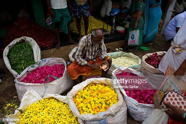 A man sells flowers in a wholesale market in Madurai