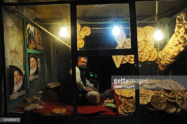 A man sells freshly baked bread displayed in the window where a picture of the recently assasinated ex Afghan president Borhaneddin Rabbani and...