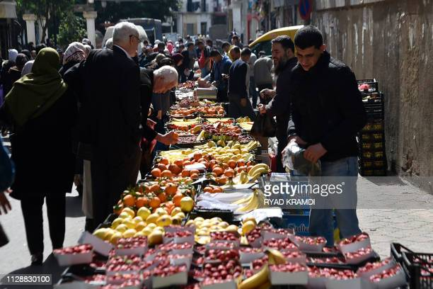 A man sells fruiits and vegetables at the Ferhat Boussaad open market in Algiers on March 6 2019