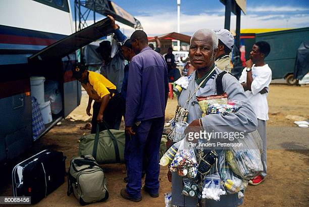 A man sells goods as passengers board to longdistance bus at Baragwanath taxi station on March 14 2005 in Soweto Johannesburg South Africa The...