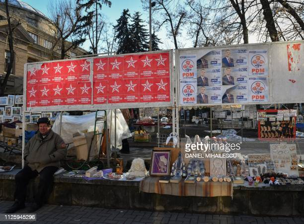 A man sells handicraft items at an outdoor market next to election posters in Chisinau on February 13 2019 The Sunday election is gearing up to be a...