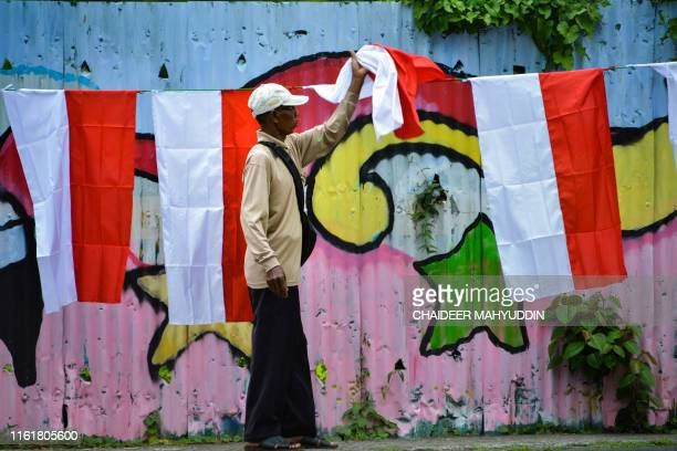 TOPSHOT A man sells Indonesian national flags on a street ahead of the Indonesia Independence Day in Banda Aceh on August 15 2019 Indonesia will mark...