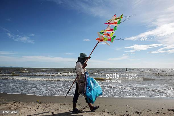 A man sells kites while walking along Bang Saen beach near Pattaya Chonburi province Thailand on Thursday May 29 2015 The Thai economy may grow 35...