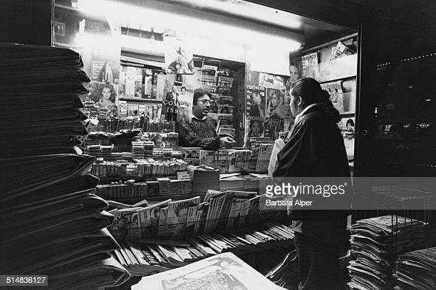 A man sells magazines and newspapers from his newsstand in New York City USA 1988