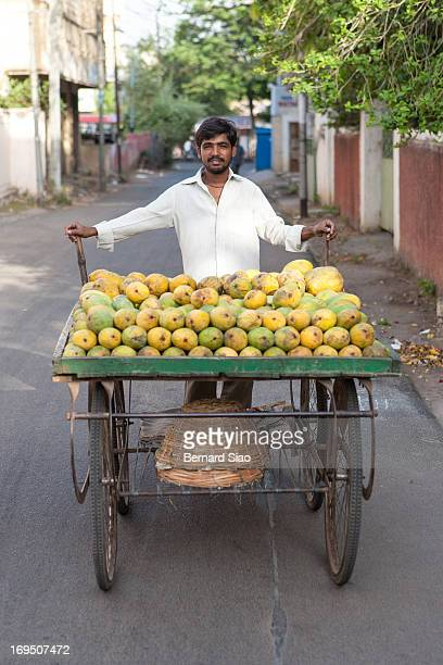 Man sells mangoes off a push cart as he walks through the small streets of Hyderabad, India, 2008