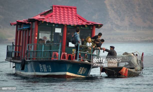 A man sells North Korean products to Chinese tourists from a boat on the Yalu river near Sinuiju opposite the Chinese border city of Dandong on April...
