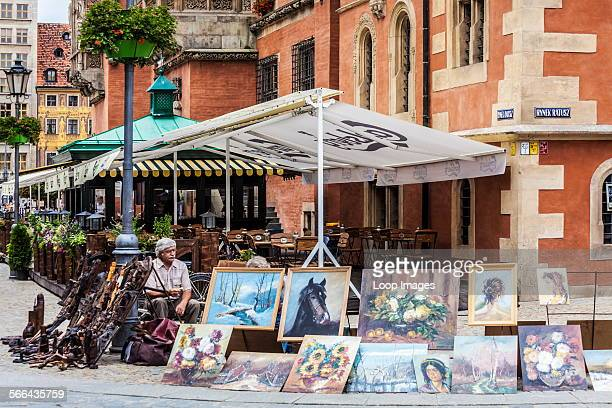 A man sells paintings and wooden carvings by the neoGothic Town Hall or Ratusz in Wroclaw's market Square