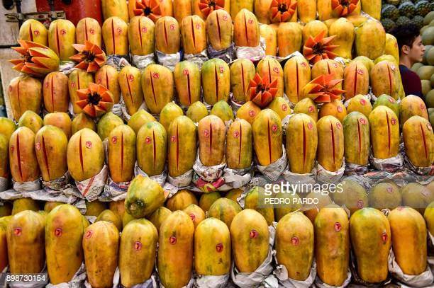 A man sells papayas at the Central de Abasto wholesale market in Mexico City on December 21 2017 Some 500000 people and 62000 vehicles a day visit...