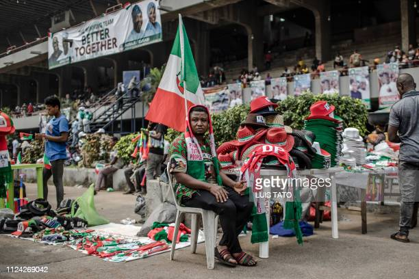 A man sells People's Democratic Party campaign merchandise as supporters gather in Lagos' Tafawa Balewa Square where the official opposition PDP...