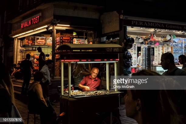 A man sells roasted chestnuts on August 15 2018 in Istanbul Turkey The Turkish Lira recovered to trade at 61 USD despite President Erdogan announcing...