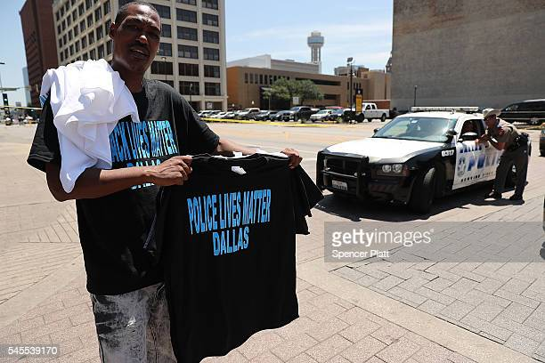 A man sells shirts near a blocked off area which is a crime investigation scene in downtown Dallas following the deaths of five police officers last...