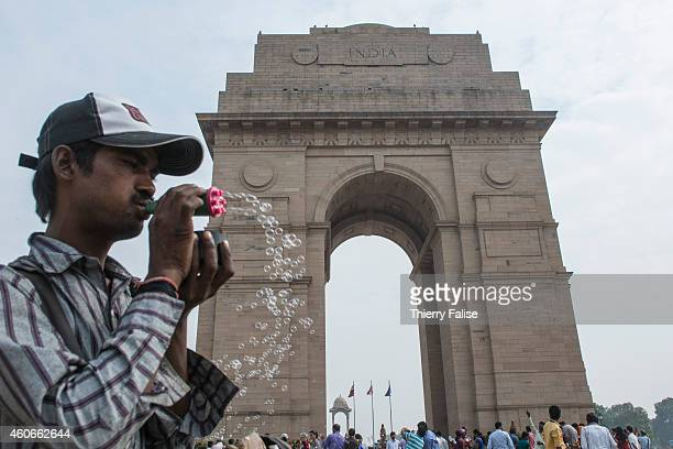 A man sells soap bubble toys near the India Gate a war memorial dedicated to Indian soldiers who died during the First World War