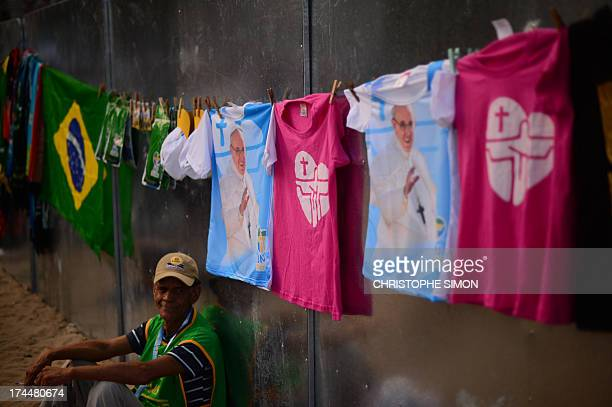 A man sells souvenirs of the visit of Pope Francis to Brazil at Copacabana beach before the arrival of the pontiff to participate in a reenactment of...