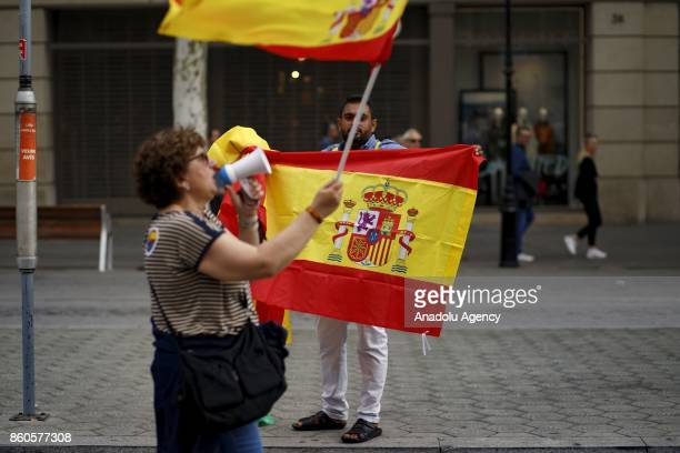 A man sells Spanish flags as a demonstrator shouts through a speaker in front of him during a demonstration supporting Spain unity on October 12 2017...