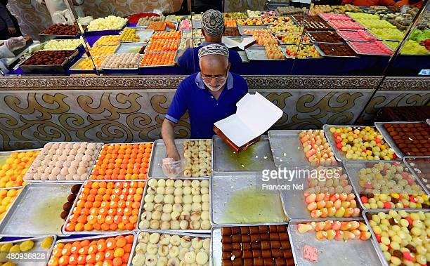 A man sells sweets ahead of Eid celebrations on July 16 2015 in Dubai United Arab Emirates The Muslim holiday Eid marks the end of 30 days of...