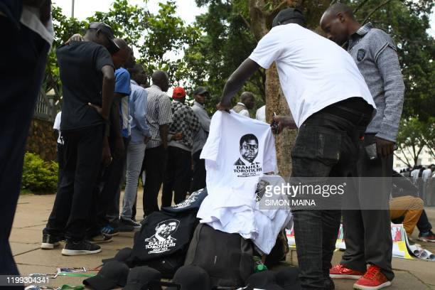 A man sells tshirts bearing the photo of late former Kenya's President Daniel Arap Moi as civilians queue to view his remains outside Parliament...