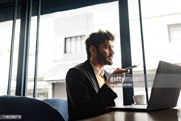 man sending audio messages at the cafe - candid forum stock pictures, royalty-free photos & images