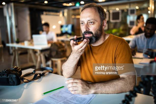 man sending voice message on smart phone from the office - speech recognition stock pictures, royalty-free photos & images