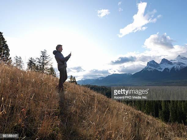 Man sends text message from grass hillside, mtns