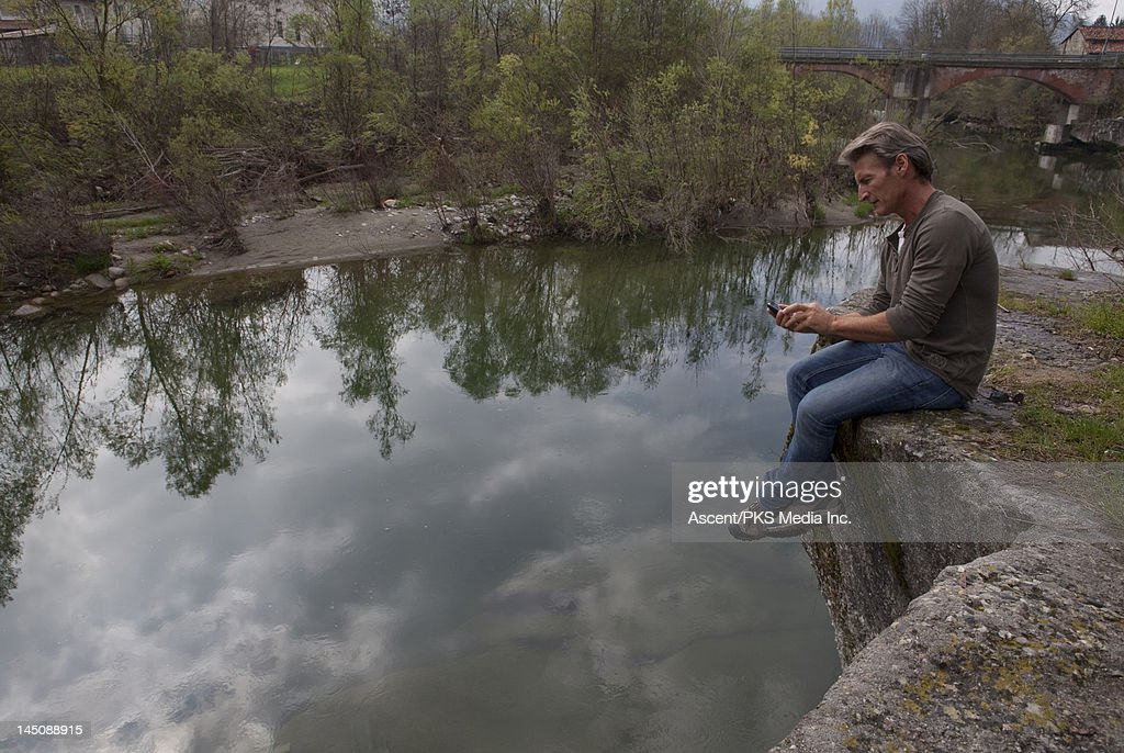 Man sends text message while perched above river : Stock Photo