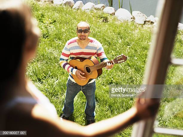 Man serenading woman at window (focus on man playing guitar)