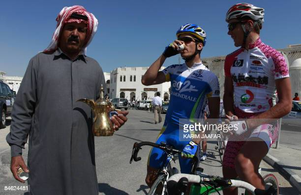Man serves Arabic coffee to cyclists before the start of the fourth stage of the Tour of Qatar from the old souk in Doha to the northern city of...