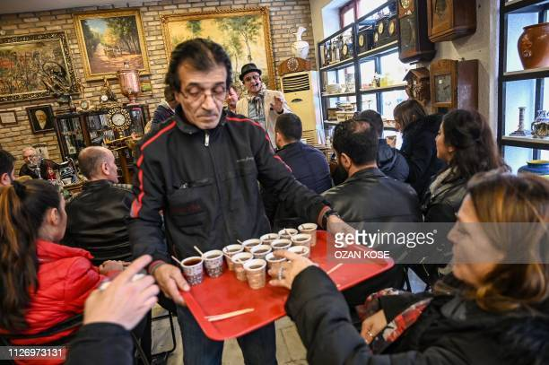 A man serves tea as auctioneer Ali Tuna shows items to the audience at an auction house in Istanbul's Balat district on February 3 2019 Auctions may...