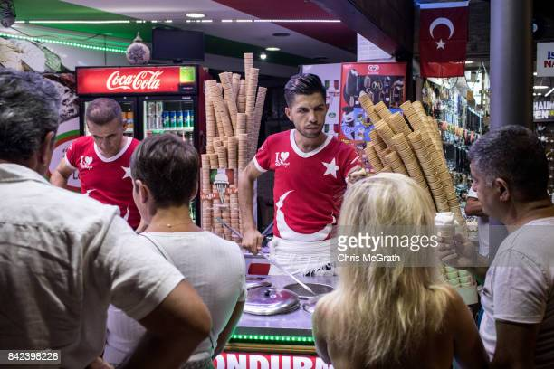A man serves Turkish ice cream to tourists on a street in the old city on September 3 2017 in Side Turkey Turkey's tourism industry spiraled into...