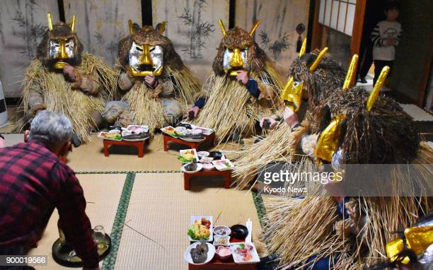 A man serves up a feast for 'Namahage' who visited his house in Oga Akita Prefecture northeastern Japan on Dec 31 2017 With demonlike masks and straw...