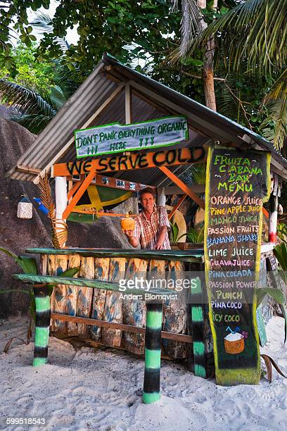 man serving a coconut drink in a beach shack - la digue island stock pictures, royalty-free photos & images