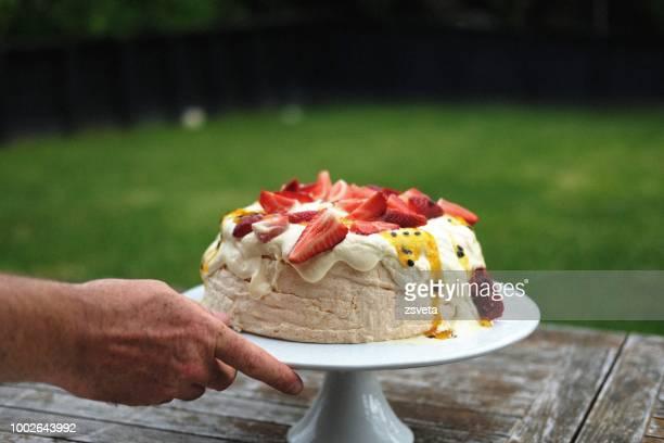 Man serving a pavlova dessert for outdoor lunch