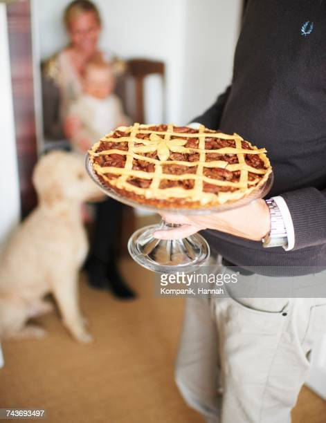a man serving a pecan pie on a cake stand for thanksgiving - first thanksgiving stock photos and pictures