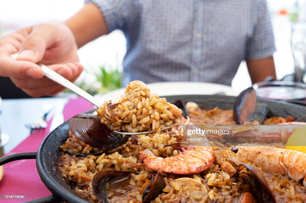 man serving a typical spanish seafood paella : Stock Photo