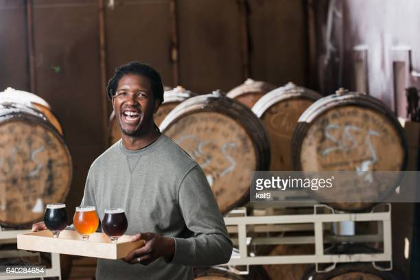 man serving beer at microbrewery - brewers stock pictures, royalty-free photos & images