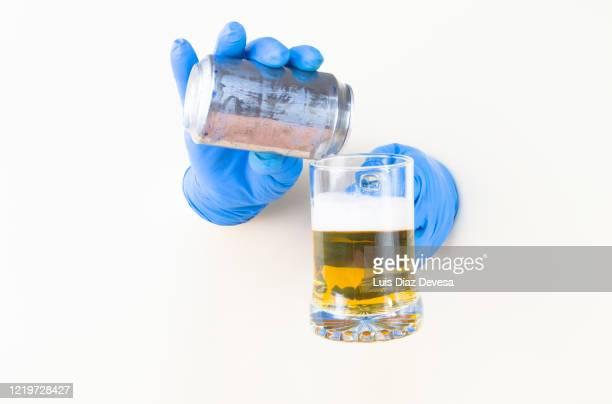 man serving beer with gloves to avoid coronavirus (covid-19) - corona beer stock-fotos und bilder