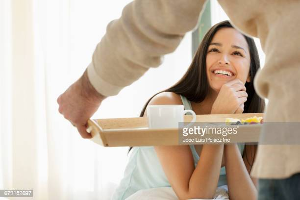 Man serving breakfast in bed to smiling Hispanic woman