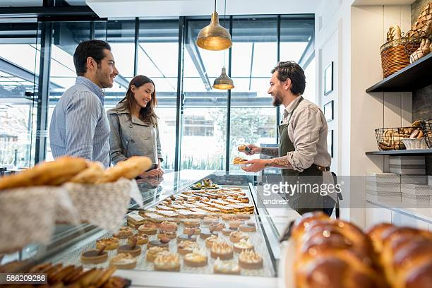 Man serving customers at a bakery