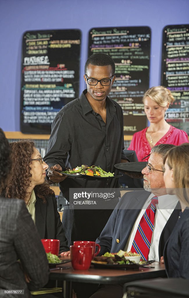 Man Serving Customers in Cafe : Stock Photo