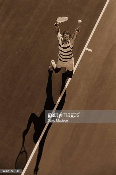 Man serving during tennis match (toned B&W)