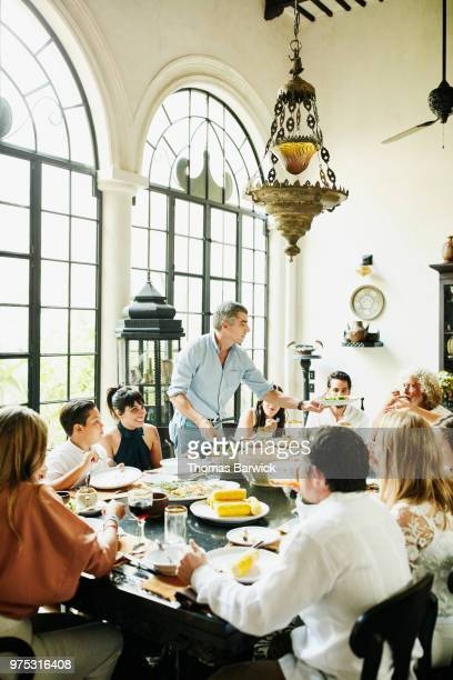 Man serving family members food at dining room table during family dinner