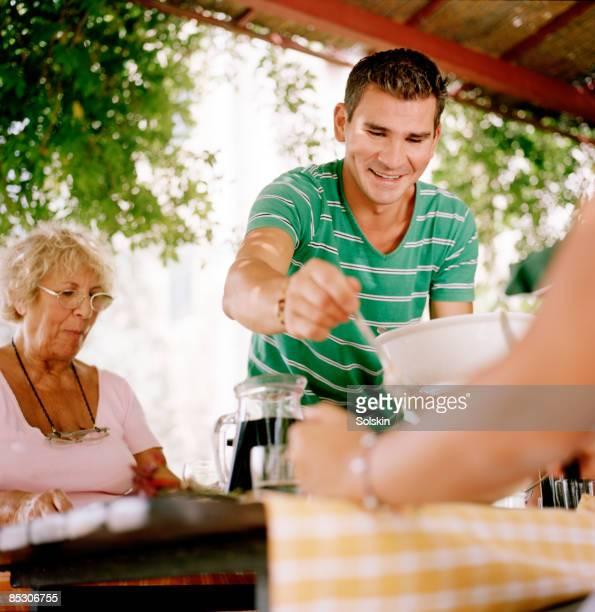 man serving food at garden dinner