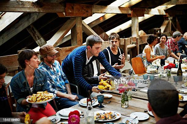 Man serving food to group of friends and family