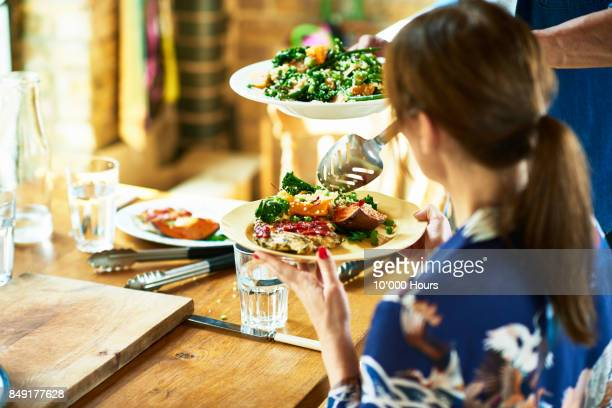 Man serving food to woman