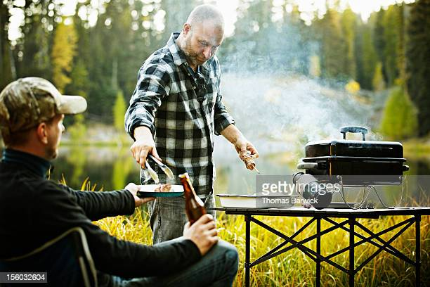 Man serving friend from outdoor barbecue